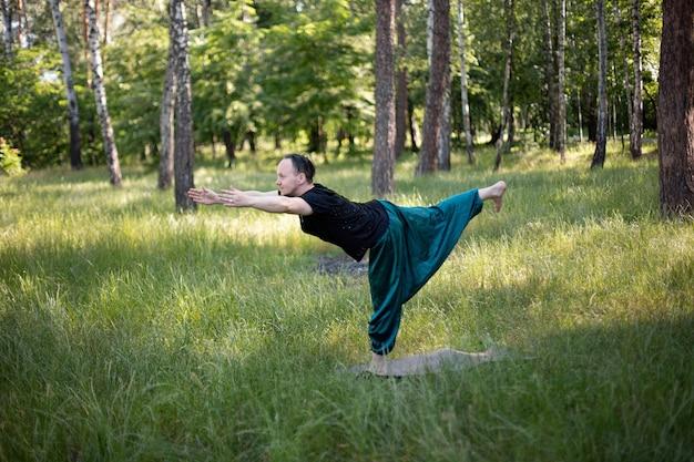 L'uomo in abiti sportivi si trova in un'asana che pratica yoga all'aperto sull'erba verde