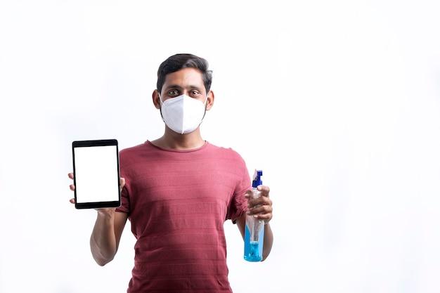 Uomo che spruzza alcol, spray disinfettante sul telefono cellulare, previene l'infezione da virus covid-19, contaminazione di germi o batteri, strofina o pulisce il telefono per eliminare, focolaio di coronavirus