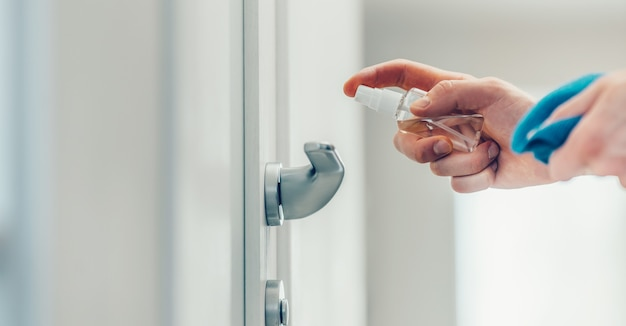 Uomo che spruzza spray antisettico sulla maniglia della porta