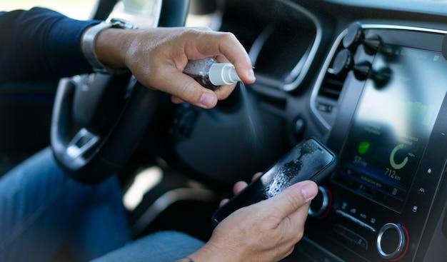 Uomo che spruzza spray disinfettante sullo schermo dello smartphone all'interno dell'auto