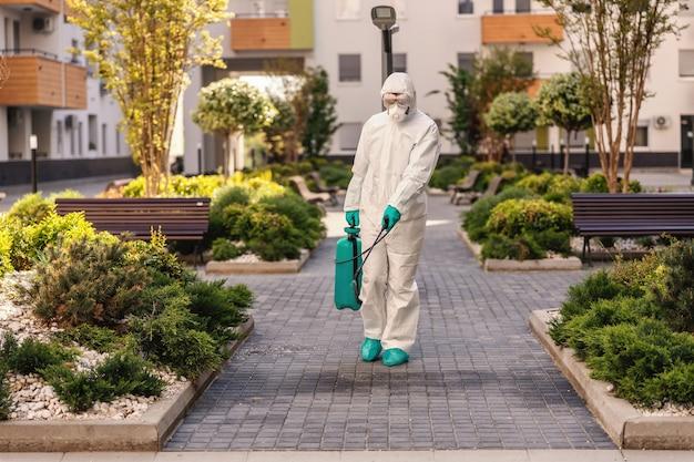 Uomo che spruzza all'aperto per prevenire la diffusione della forma di coronavirus