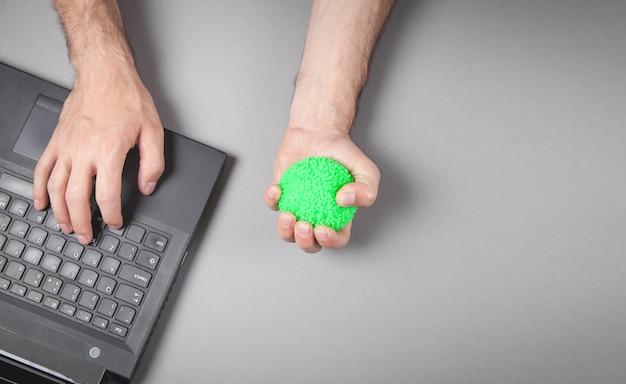 Uomo che stringe la palla antistress mentre si lavora con il computer portatile