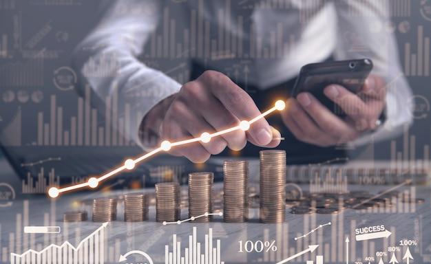 Uomo che impila monete con un grafico di profitto.