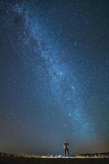 L'uomo sta sullo sfondo delle stelle nel cielo. notte