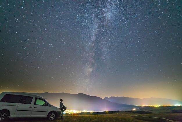 L'uomo sta vicino alla macchina sullo sfondo del cielo stellato. notte