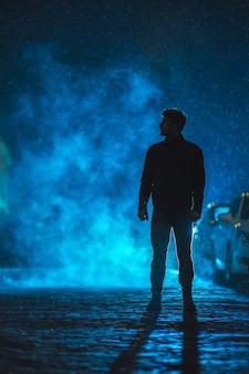 L'uomo sta sulla strada fumosa. serata notturna. colpo con teleobiettivo