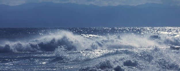 Uomo in piedi contro il mare su un molo con grande onda che batte con schizzi in una tempesta