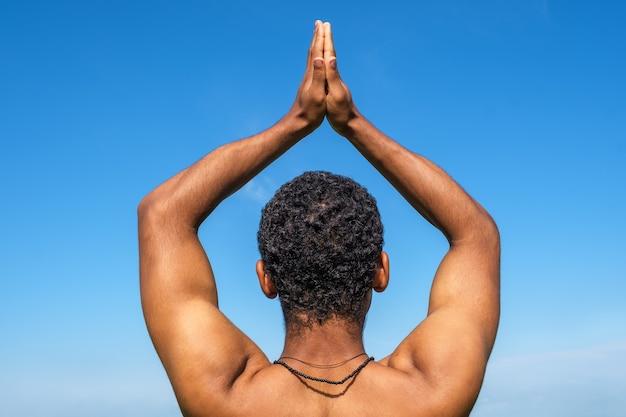 Uomo in piedi di nuovo alla telecamera in posa yoga su sfondo blu cielo in estate