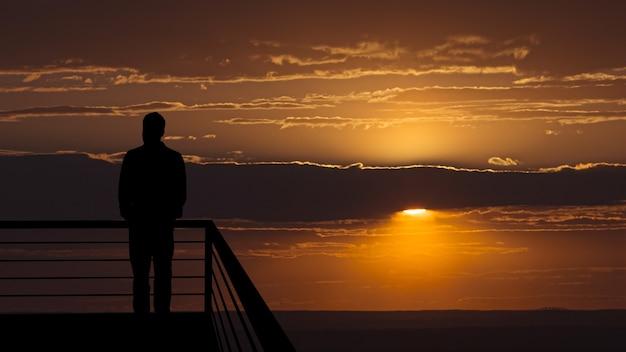 L'uomo in piedi sul balcone sullo sfondo panoramico del tramonto