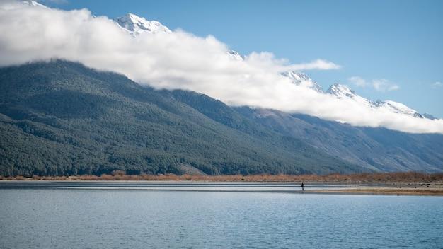 Uomo in piedi sulla riva del lago di fronte a grandi montagne avvolte da nuvole basse glenorchynew zealand