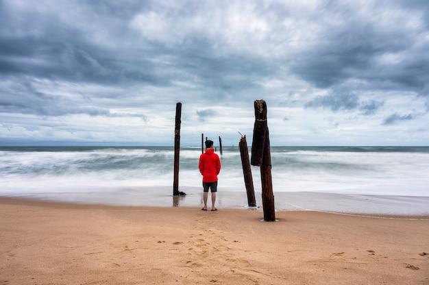 Uomo in piedi sulla spiaggia e la grande onda che colpisce il ponte di legno di decadimento durante le tempeste a pilai beach, phang nga