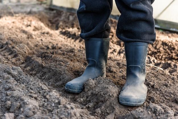 Uomo in piedi con gli stivali sul suolo