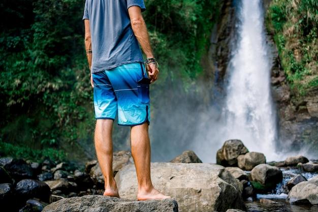 Uomo in piedi da un fiume davanti a una cascata. turrialba, costa rica