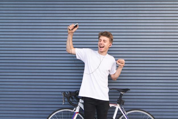 Uomo in piedi da una bicicletta bianca, ascoltando musica in cuffia con uno smartphone in mano