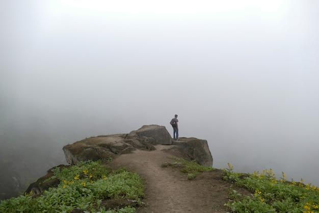 Uomo in piedi su una scogliera in una valle guardando la strada nebbiosa dei fiori