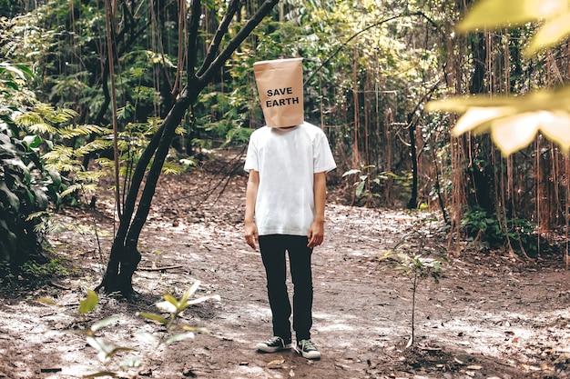Un uomo in piedi e coprendosi il viso con un cartoncino con la scritta save earth