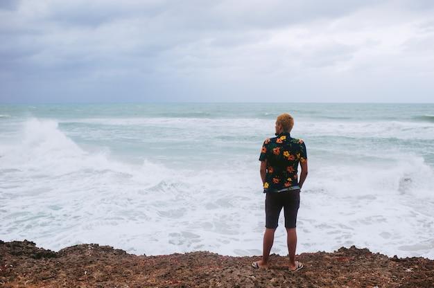 Uomo in piedi sull'orlo dell'abisso di fronte al mare con grande