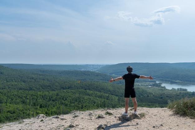 Uomo in piedi su un bordo di una scogliera e guardando il terreno bello e accidentato intorno a lui. stile di vita in viaggio avventuroso. voglia di vagabondaggio del concetto. vacanze attive per il fine settimana natura selvaggia all'aperto.
