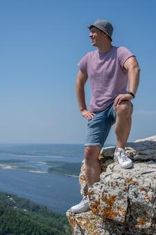 Uomo in piedi sul bordo di una scogliera, sorridente e guardando il terreno bello e accidentato intorno a lui. stile di vita in viaggio avventuroso. voglia di vagabondaggio del concetto. vacanze attive per il fine settimana natura selvaggia all'aperto.