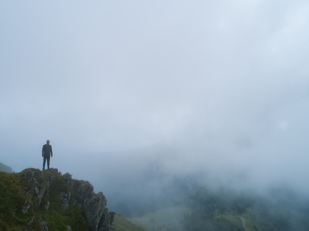 L'uomo in piedi sulla montagna nebbiosa