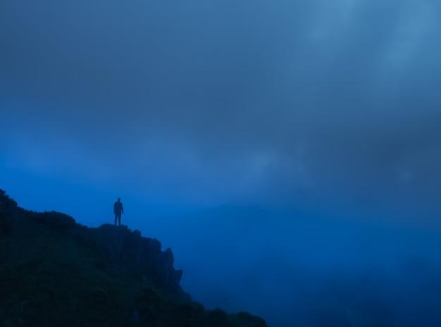 L'uomo in piedi sulla roccia nebbiosa. sera notte