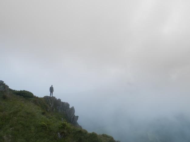 L'uomo in piedi sulla roccia nebbiosa