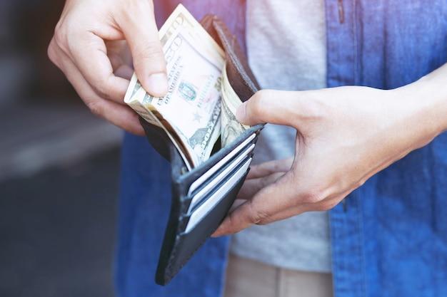 Uomo in piedi tenendo il portafoglio nero pieno di soldi
