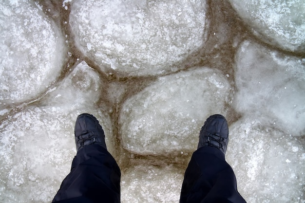Uomo in piedi sul ghiaccio. struttura di ghiaccio un bellissimo modello con i piedi della persona
