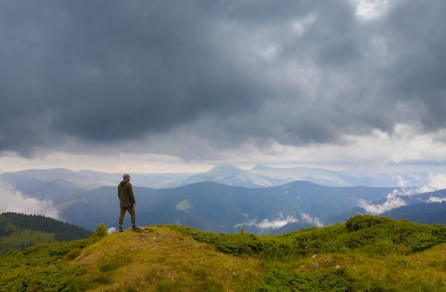 L'uomo in piedi sulla montagna contro le nuvole piovose