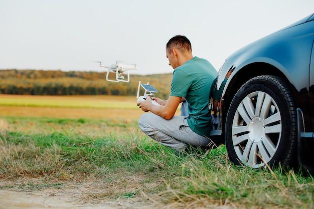 Un uomo in piedi vicino all'auto lancia un drone. volo con drone in campo giallo