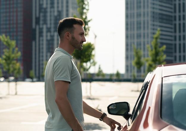L'uomo in piedi vicino alla macchina nel parcheggio