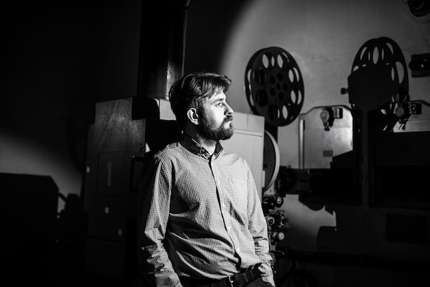 Uomo in piedi vicino a un proiettore cinematografico in sala proiezionista