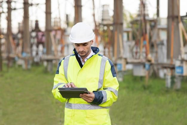 Uomo in piedi vicino alla sottostazione ad alta tensione e digitando sul dispositivo ingegnere maschio in uniforme e casco