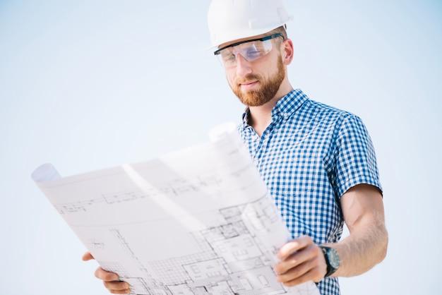 Uomo in piedi e leggendo il progetto