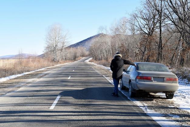 Uomo in piedi sulla strada accanto alla sua auto guardando avanti