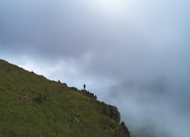 L'uomo in piedi sulla roccia tra le nuvole