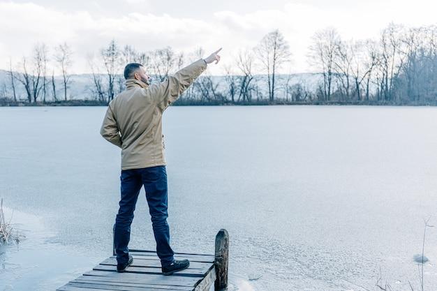 Uomo in piedi su un piccolo molo di legno vecchio, godendo il tramonto invernale su un lago ghiacciato.