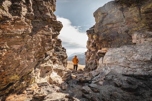Uomo in piedi su un vertice tra le rocce nel parco nazionale delle montagne rocciose e guardando oltre la catena montuosa in una giornata fredda e ventosa