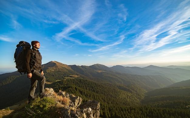 L'uomo in piedi sulla montagna soleggiata