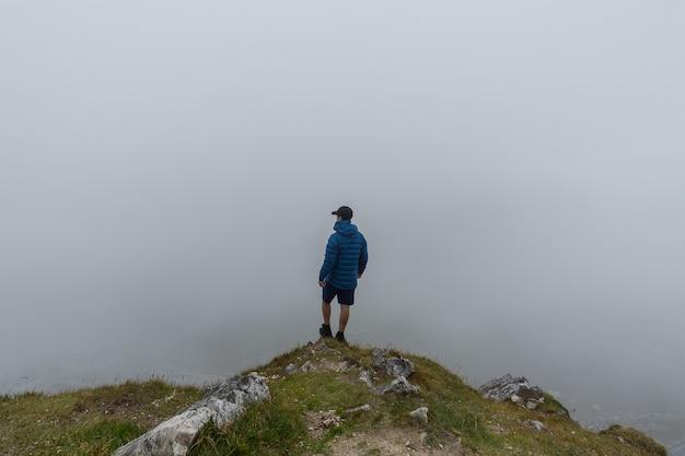 Uomo in piedi in cima alla montagna ammirando il paesaggio con la nebbia
