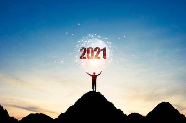 Un uomo in piedi sulla cima della montagna e alza due mani per portare il mondo con connessione e numero 2021 sul cielo blu. è il simbolo dell'inizio e del benvenuto del felice anno nuovo 2021.
