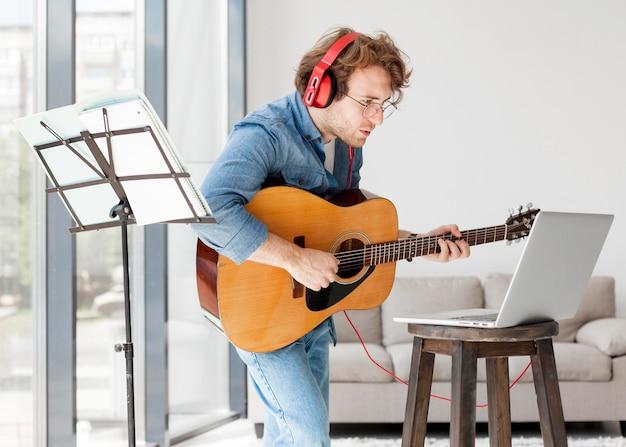 Uomo in piedi e cercando di imparare la chitarra