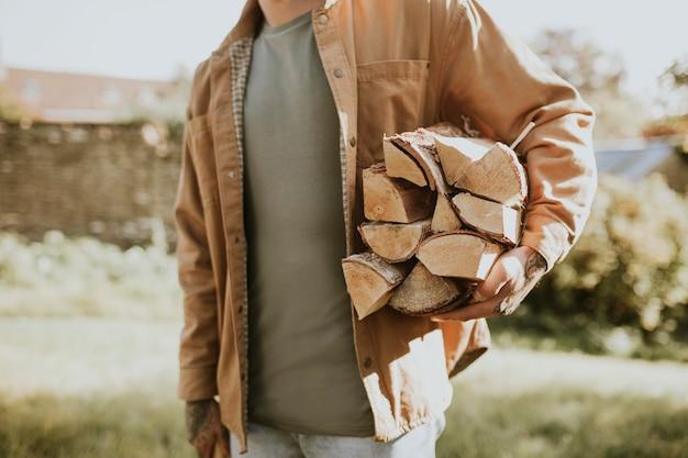 Uomo in piedi con ascia e legname tritato e moncone in una fattoria