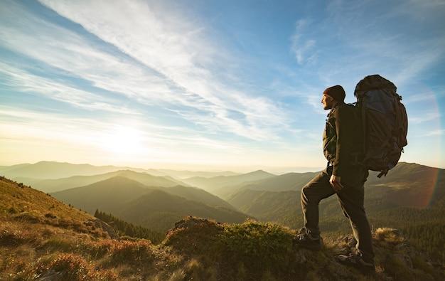 L'uomo in piedi con uno zaino da campeggio sulla roccia con un'alba pittoresca