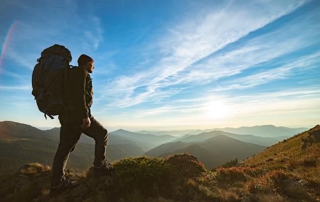 L'uomo in piedi con uno zaino da campeggio sulla roccia con un pittoresco tramonto