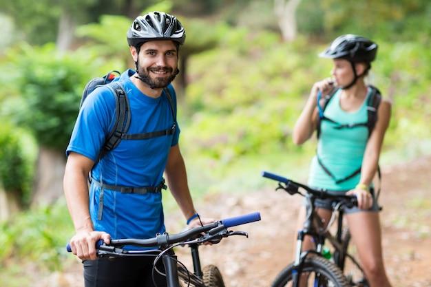 Uomo che sta con il mountain bike in foresta