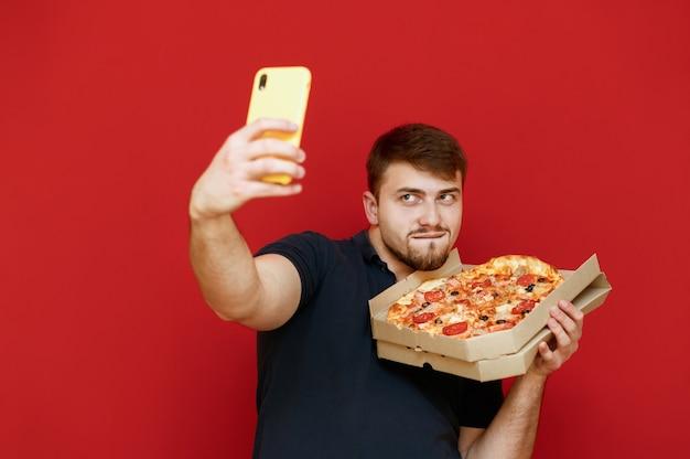 Uomo in piedi con la scatola della pizza in mano e fare foto