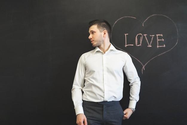 Uomo in piedi sulla parola amore sulla lavagna e guardando lontano. fidanzato in attesa dell'amore
