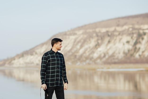 L'uomo si trova sulla riva del fiume con uno splendido scenario di montagna