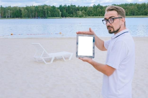 Un uomo si trova sulla spiaggia con un tablet simulato tra le mani. sullo sfondo di una sedia a sdraio e sabbia con acqua e foresta.